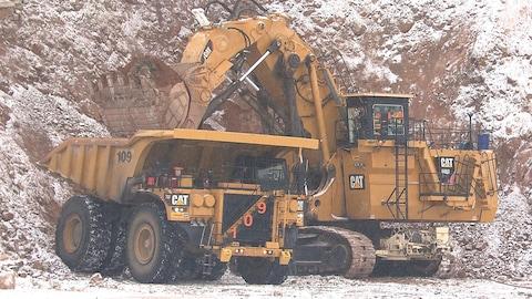 Une chargeuse verse du minerai dans un camion