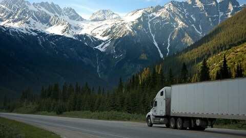 Sur la route, dans le fond les montagnes enneigées