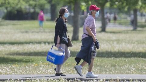 Un homme et une femme portant un masque marchent dans un parc.