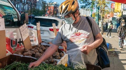 Isang lalake na naka-mask at bike helmet na namimili ng gulay.