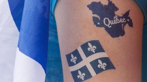 Une femme arbore des tatouages de la carte et du drapeau du Québec, dans le cadre des festivités de la fête nationale du Québec.