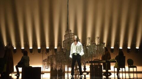 Emmanuel Schwartz se tient debout derrière un lustre géant. On aperçoit également d'autres acteurs de dos, dans l'ombre, assis sur une chaise ou sur un siège.