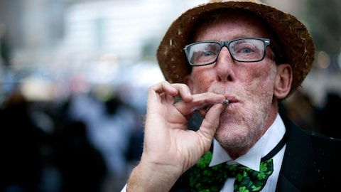 Un homme portant un chapeau et un noeud papillon orné de trèfles fume un joint de cannabis.