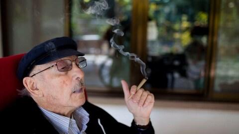 Un aîné portant un béret fume du cannabis médicinal assis dans un fauteuil dans un centre de soins de longue durée en Israël