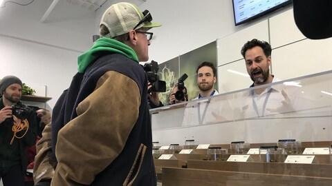 Un homme qui porte un blouson de sport parle à un autre homme au comptoir d'un magasin.