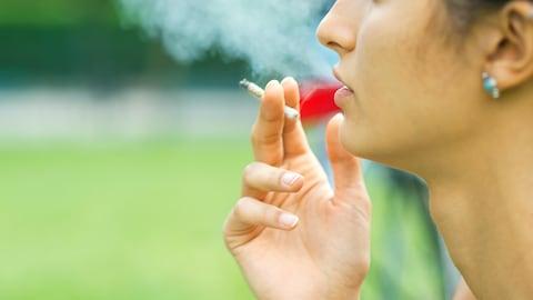 Une femme fume une cigarette de marijuana.