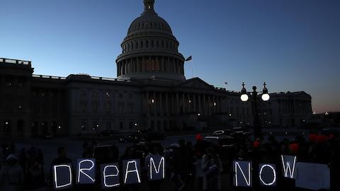 Des manifestants tiennent des lettres formant la locution Dream Now (Rêver maintenant) devant le Capitole, à la tombée du jour.