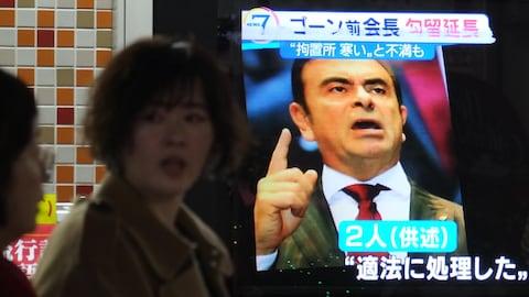 Des femmes japonaises passent devant un écran présentant une image de Carlos Ghosn lors d'un bulletin de nouvelles.