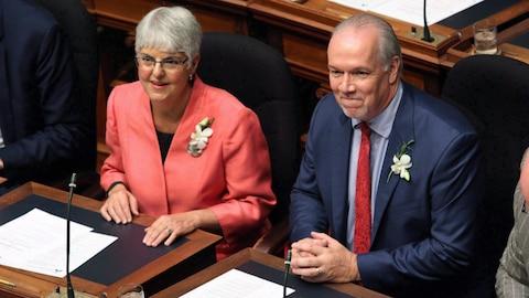 Une femme à gauche à côté d'un homme à droite.assis à l'intérieur d'une chambre législative.