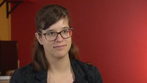 Une jeune femme est devant un mur rouge dans les bureaux de l'organisme pour lequel elle travaille.