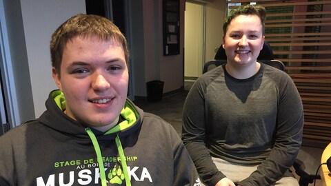 Portrait de deux jeunes hommes souriants. Ils sont assis à côté d'une table dans un studio de radio