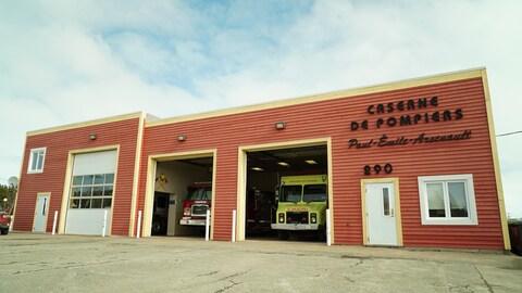 La caserne de pompiers Paul-Émile Arsenault à Cap-aux-Meules. Deux portes sont ouvertes. On peut voir deux camions à l'intérieur.