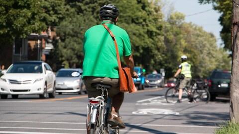 Un cycliste circule dans les rues et porte un casque.