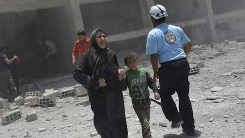 Des civils sont évacués par des Casques blancs après qu'un édifice eut été la cible de frappes aériennes dans la ville de Deraa, en Syrie.