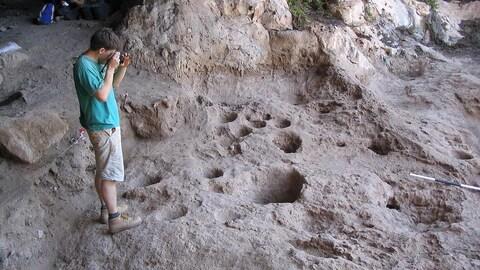 On voit les cavités creusées dans le sol de la caverne de Raqefet. À gauche, un homme prend une photo.