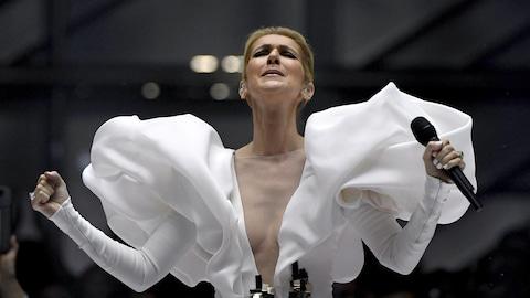 La chanteuse Céline Dion, microphone en main et vêtue d'une robe blanche, donne une prestation sur une scène lors de la soirée de remise des prix Billboard, à Las Vegas, en mai 2017.