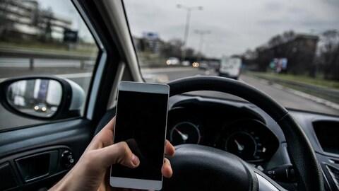 Une personne tenant un téléphone cellulaire au volant.