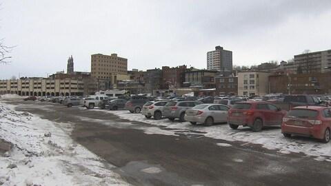 Un stationnement avec des véhicules. Derrière, on peut voir le centre-ville de Chicoutimi.