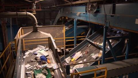 Des matières recyclables défilent sur des tapis roulants à l'intérieur d'un centre de récupération.