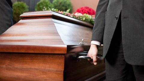 Des hommes en habit soulèvent un cercueil.