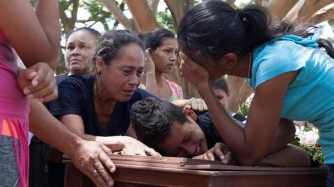 Des gens pleurent, appuyés sur le cercueil d'Abraham Duran, l'un des prisonniers qui est mort lors de l'émeute d'une prison au Venezuela.