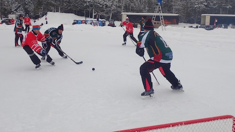Deux joueurs se disputent la rondelle alors qu'un joueur garde le but.