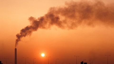 La cheminée d'une usine émet de la fumée.