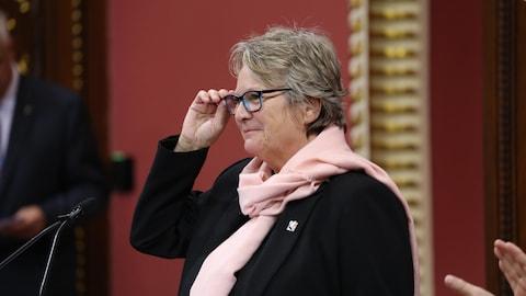 Mme Rouleau ajuste ses lunettes, debout dans le Salon rouge de l'Assemblée nationale.