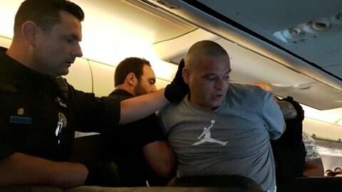 Charalabos Nassios, portant un chandail gris, lors de son arrestation à bord d'un avion de Sunwing.
