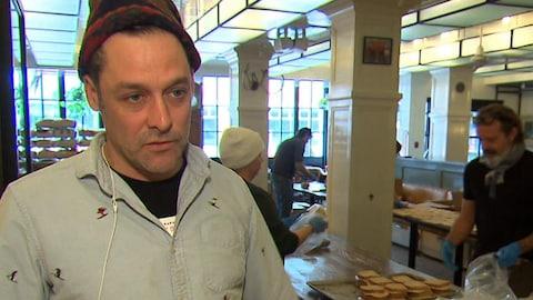 Le chef parlant à la caméra avec en arrière-plan, des bénévoles qui préparent des sandwichs.
