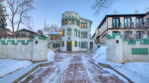 Une grande maison verte et blanche en hiver.