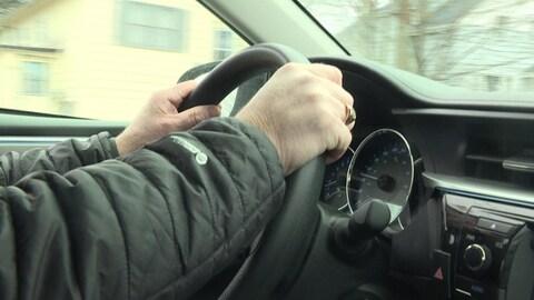 Les mains d'un homme sur le volant d'une voiture