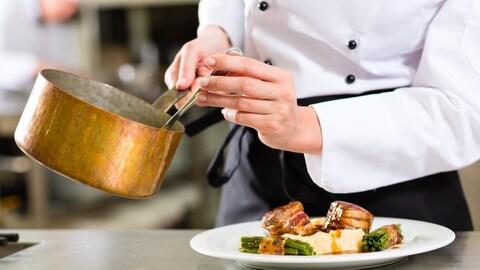 Un chef dispose de la sauce dans un plat de viande dans une cuisine de restaurant.