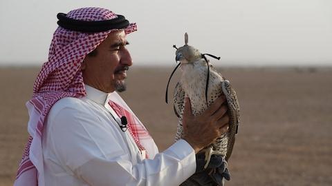 Le cheik Faisal tient son faucon sur son avant-bras.