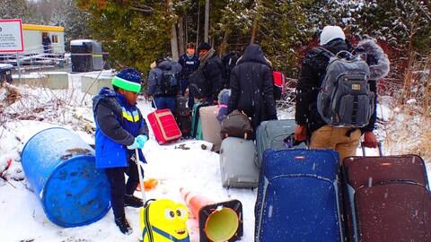 Un groupe de Nigérians traverse illégalement la frontière canado-américaine sur le chemin Roxham.