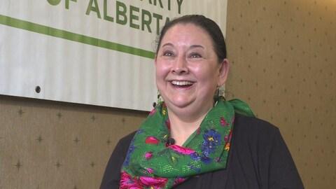 Cheryle Chagnon-Greyeyes qui a été élue chef du Parti vert de l'Alberta porte un foulard et sourit devant l'appareil photo.