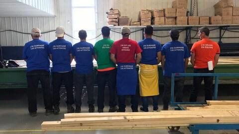 Huit hommes sont de dos dans une usine de bois et portent des t-shirts indiquant leurs forces au sein de l'entreprise.