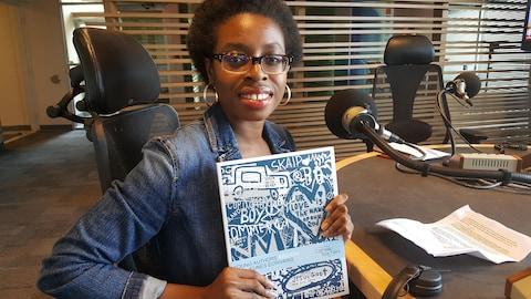 Une jeune fille à la peau foncée tient dans ses mains un cahier bleu et blanc dans lequel se trouve les écrits de sa pièce de théâtre.