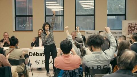 周六,唐人街有史以来第一次主办市政选举辩论会,主办机构代表赵秀媚(中间举起拳头的女士)在会议结束时。