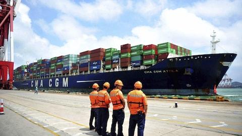 Des débardeurs regardent un bateau sur le quai d'un port chinois.
