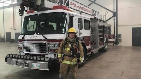 Un homme en habit de pompier devant un camion de pompier.