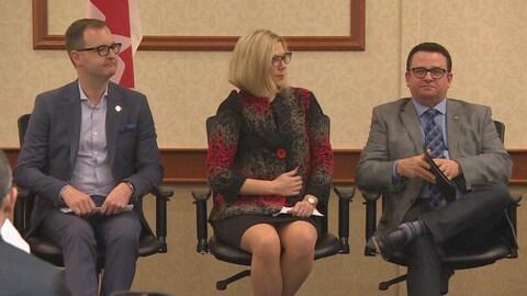Trois personnes assises sur une estrade, lors d'une conférence dans un hôtel de Winnipeg.