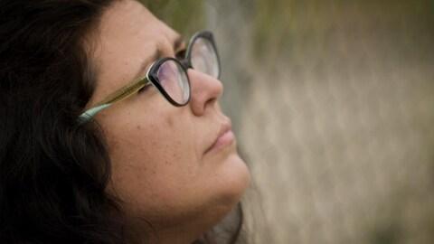 Christie-Anne Blondeau assise contre une clôture et regarde vers le haut avec un air triste