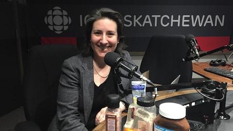 Une femme souriante dans un studio de raio, avec des objets disposés devant elle. On reconnait un pot de Nutella, un couteau, du sel, du poivre et des chaufferettes chimiques pour les mains.
