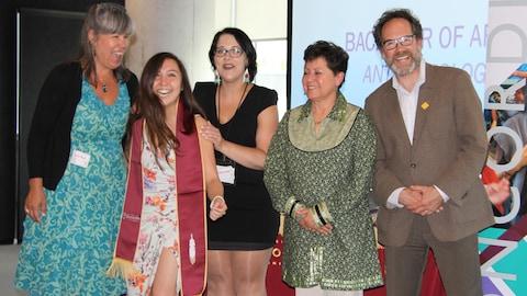 Christine pose avec les membres de l'équipe du centre de ressources pour étudiants lui on offert l'étole officielle de l'Université Concordia.