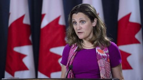 Le portrait d'une femme devant quatre drapeaux canadiens.