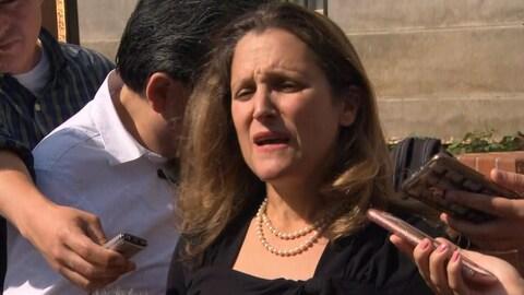 La ministre des Affaires étrangères Chrystia Freeland entourée de journalistes.