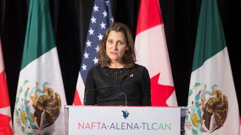 Chrystia Freeland parle devant les drapeaux du Canada, du Mexique et des États-Unis.