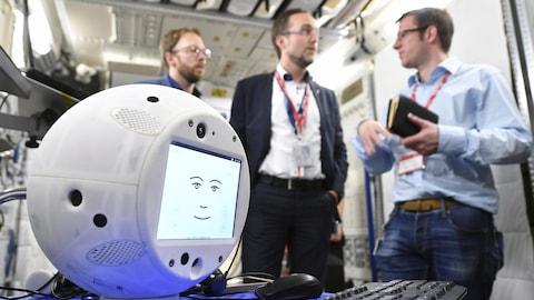 Des chercheurs discutent à l'arrière-plan alors qu'on peut voir à l'avant-plan le robot Cimon, qui a la forme d'un gros ballon de basketball blanc, avec un écran sur lequel apparaît un visage souriant dessiné à l'aide de traits simples.
