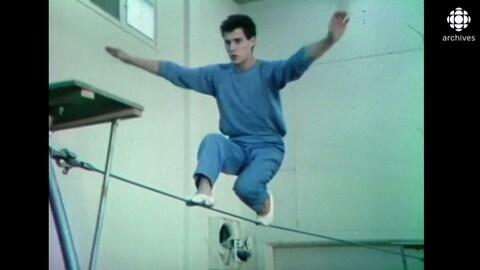 Jeune homme en équilibre sur un fil de fer.